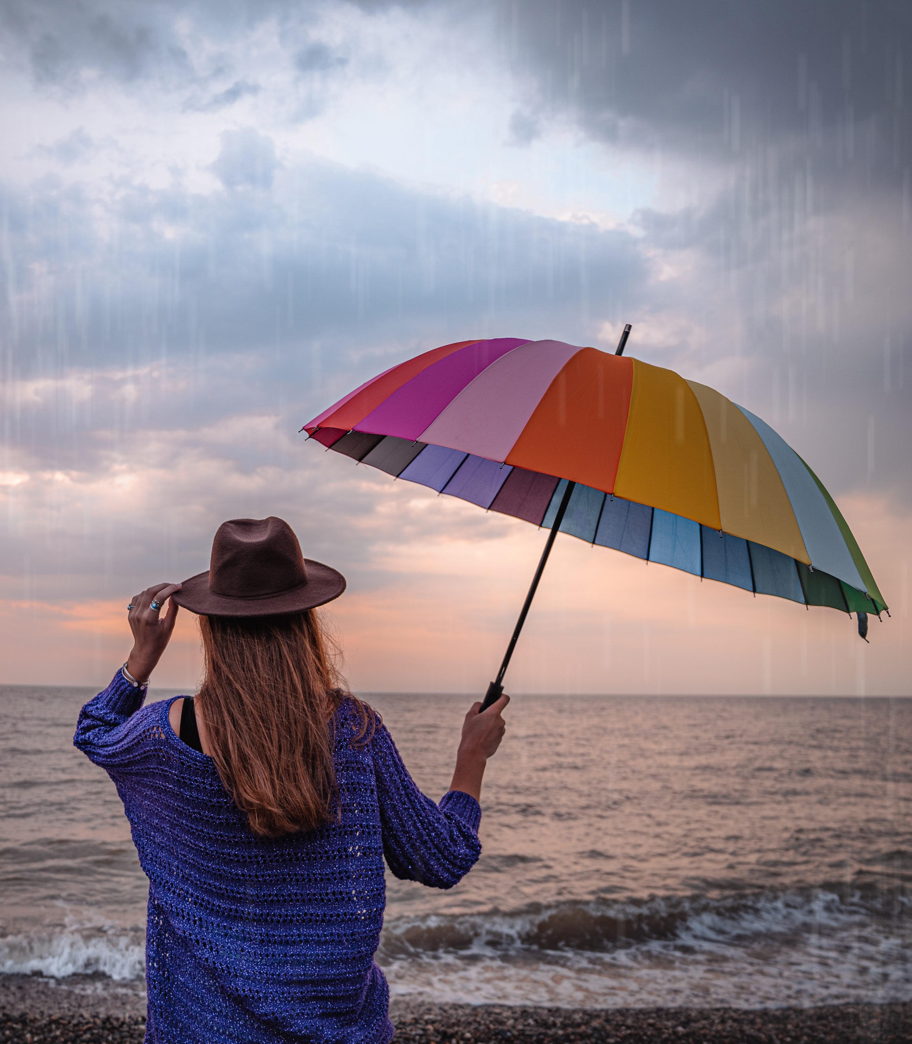 Une femme devant la mer sous un parapluie arc-en-ciel et un chapeau sous la pluie